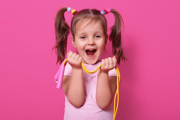 Lachende süße mädchen trägt rose t-shirt, steht isoliert auf rosa, halten helle springseil in den händen. glückliches kind mit geöffnetem mund spielt gern mit neuem springseil. kindheitskonzept.