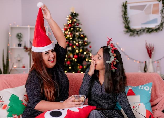 Lachende tochter mit stechpalmenkranz schaut auf die mutter, die eine weihnachtsmütze über dem kopf hält und auf der couch sitzt und die weihnachtszeit zu hause genießt
