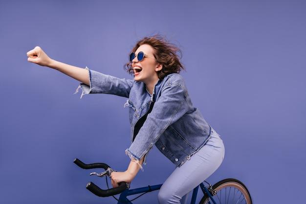Lachende trendige dame, die auf fahrrad sitzt und hand winkt. porträt des entzückenden kaukasischen weiblichen radfahrers.