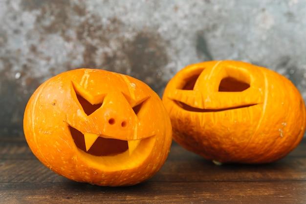 Lachende und lächelnde geschnitzte halloween-kürbise auf schreibtisch