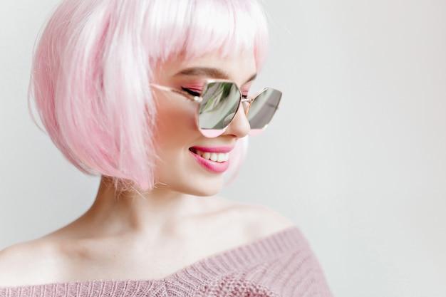 Lachende verträumte junge frau trägt funkelnde sonnenbrille und peruke. innennahaufnahmeporträt des lächelnden ekstatischen mädchens mit rosa haaren.