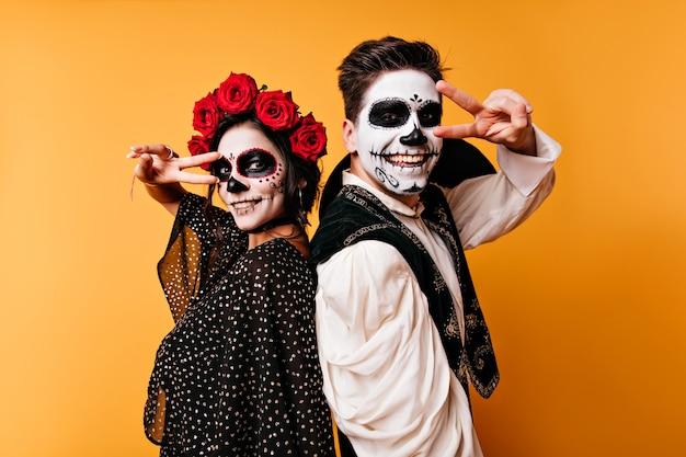 Lachende zombies stehen auf gelber wand. nettes paar mit mexikanischem make-up, das an halloween-partei kühlt.