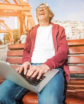 Lachender älterer mann, der auf bank mit einem offenen laptop auf seinem schoss sitzt