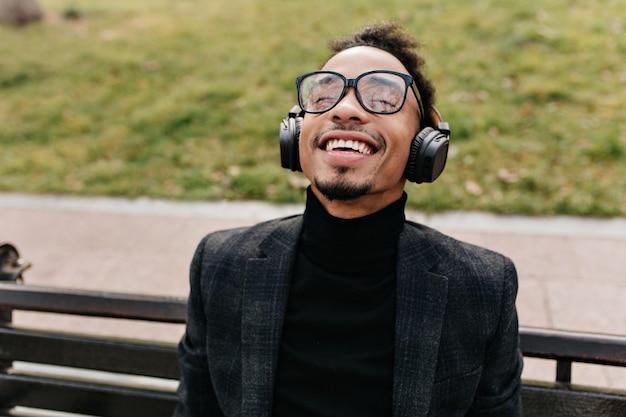 Lachender afrikanischer mann, der auf hölzerner bank mit grünem rasen aufwirft. glücklicher schwarzer kerl in der brille, die musik mit geschlossenen augen und lächelnd hört.
