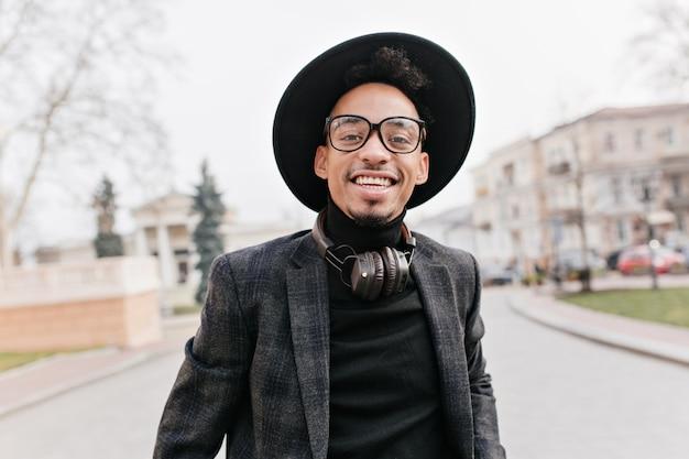 Lachender afrikanischer mann mit der trendigen lockigen frisur, die hut trägt. außenfoto des männlichen modells mit dunkler haut, die spaß beim erkunden der stadt hat.