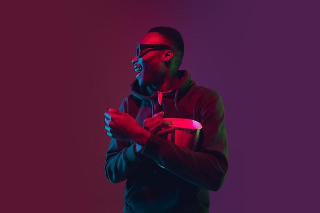 Lachender afroamerikaner mans porträt auf farbverlaufsstudio im neonlicht