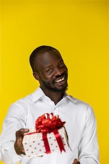 Lachender bärtiger junger afroamerikaner mit einem geschenk