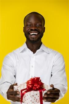 Lachender bärtiger junger afroamerikanischer kerl hält ein geschenk in zwei händen im weißen hemd