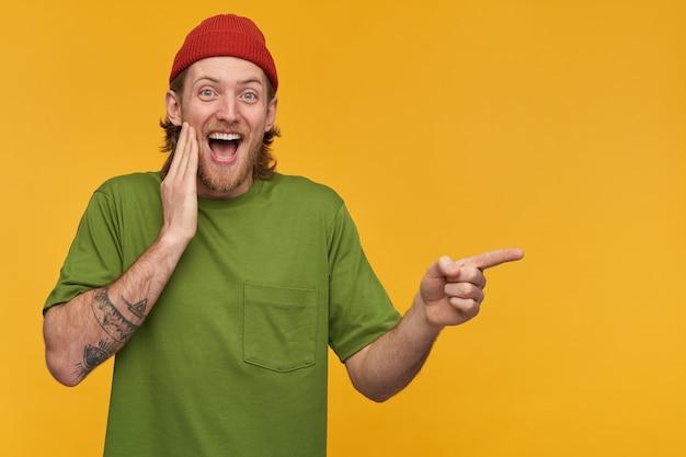 Lachender bärtiger kerl mit blonden haaren. trägt grünes t-shirt und rote mütze. hat tätowierungen. und zeigefinger nach rechts auf den kopierbereich, isoliert über der gelben wand