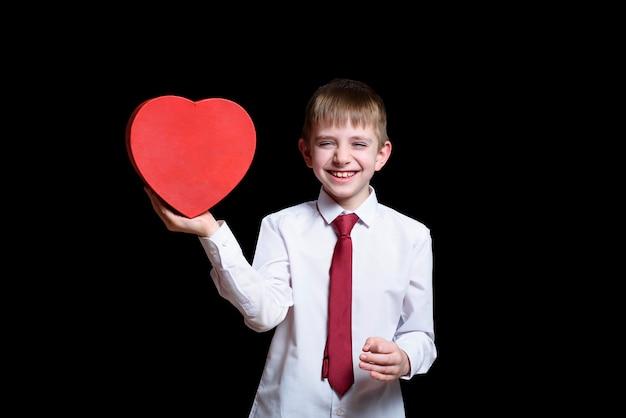 Lachender blonder junge in einem hemd und in einer bindung, die ein rotes herz halten, formte kasten. liebes- und familienkonzept.