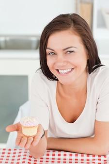 Lachender brunette, der einen kleinen kuchen zeigt