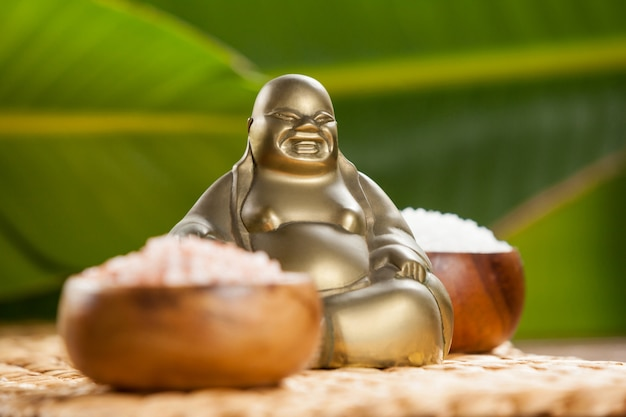 Lachender buddha-figur und meersalz in holzschale