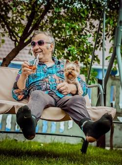 Lachender großvater mit dem hund in solenyh-gläsern