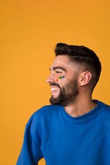 Lachender gutaussehender mann mit lgbt-regenbogen auf gesicht