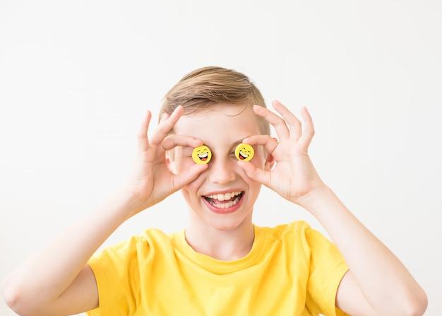 Lachender junge, der in seiner hand ein lustiges gelbes lächeln anstelle der augen hält