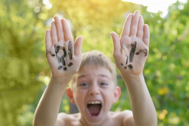 Lachender junge mit den angehobenen händen schriftliche frage- und ausrufezeichen.