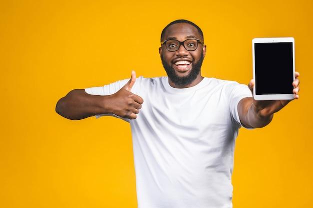 Lachender junger afroamerikaner, der einen touchpad-tablet-pc auf hält. daumen hoch.