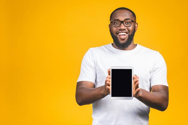 Lachender junger afroamerikaner, der einen touchpad-tablet-pc auf hält.
