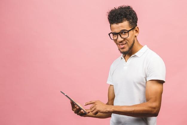 Lachender junger afroamerikaner-mann, der einen touchpad-tablet-pc hält, der gegen rosa hintergrund isoliert wird