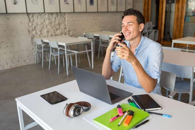 Lachender junger attraktiver mann beschäftigt, auf smartphone zu sprechen