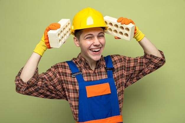 Lachender junger männlicher baumeister, der uniform mit handschuhen trägt, die ziegelsteine um den kopf halten