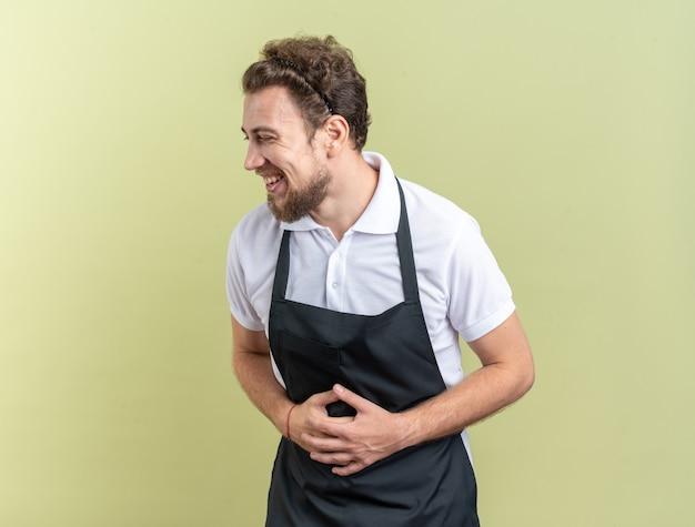Lachender junger männlicher friseur in uniform packte den magen isoliert auf olivgrüner wand