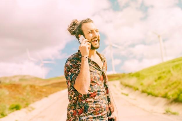 Lachender junger mann, der am telefon in der landschaft sich unterhält