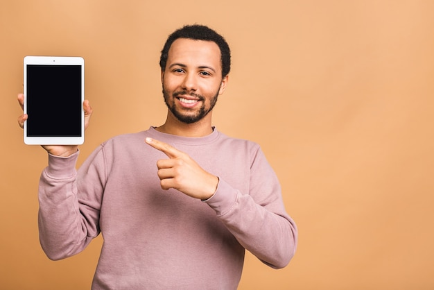Lachender junger mann, der einen touchpad-tablet-pc auf isoliert über beige hält.