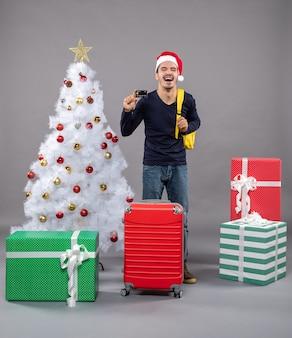 Lachender junger mann, der karte hält, die nahe weihnachtsbaum auf grau lokalisiert steht