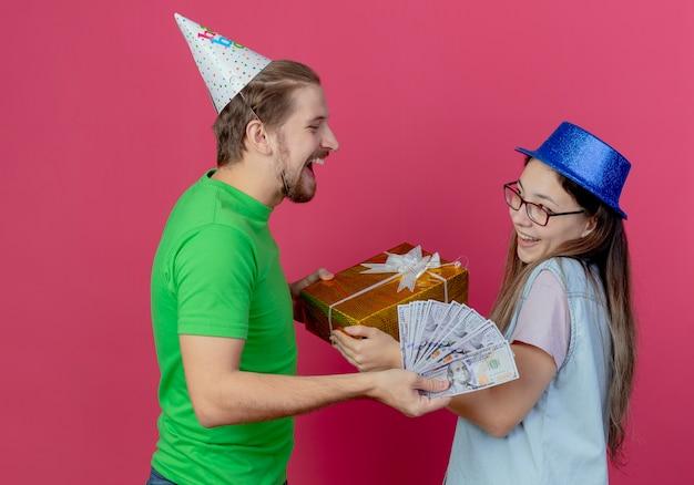 Lachender junger mann, der partyhut trägt, bietet dem erfreuten jungen mädchen, das blauen partyhut trägt, geld an, um geschenkbox isoliert auf rosa wand zu nehmen