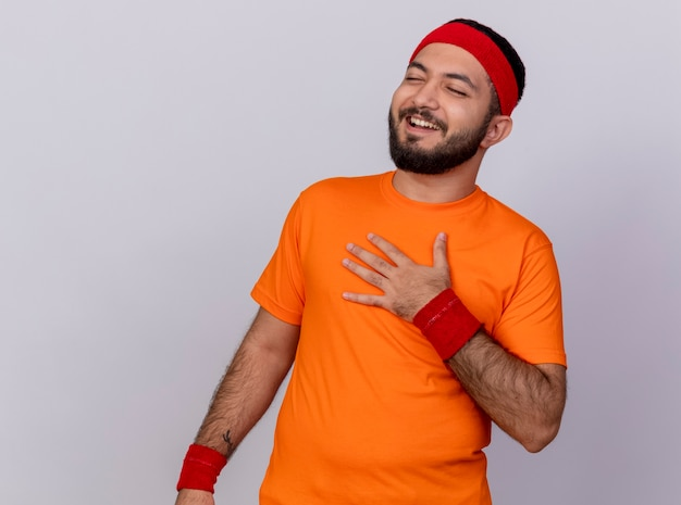 Lachender junger sportlicher mann mit geschlossenen augen, der stirnband und armband trägt, die hand auf brust setzen