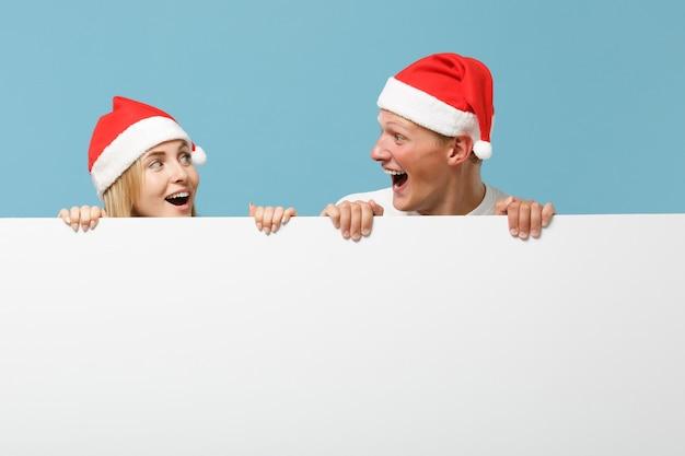 Lachender junger weihnachtsmann-paarfreunde kerl und frau in der weihnachtsmütze