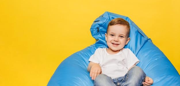 Lachender kleiner junge auf einer gelben wand, die in einem blauen stuhl sitzt.