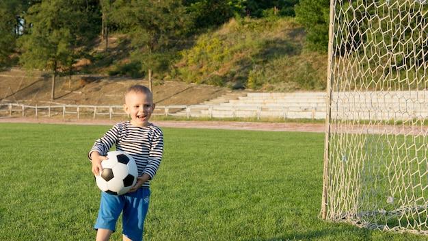 Lachender kleiner junge mit einem fußball in seinen händen, der sich amüsiert, auf einem grünen sportplatz im abendlicht zu spielen