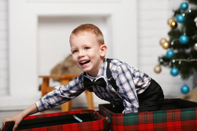 Lachender kleiner junge spielt versteckt in einem roten karierten koffer im innenraum mit weihnachtsdekorationen
