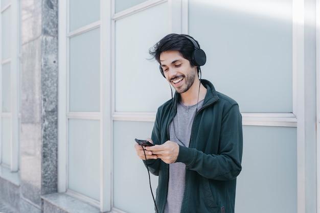 Lachender mann, der smarpthone auf straße verwendet