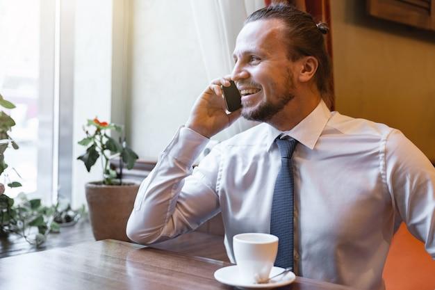 Lachender mann, der um den handy sitzt im restaurant im innen tragen des weißen hemdes ersucht