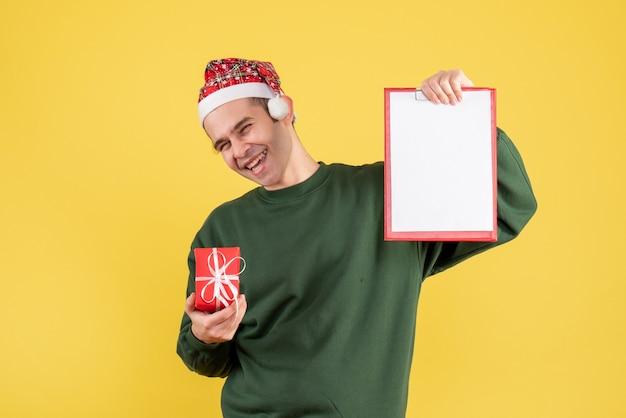 Lachender mann der vorderansicht mit grünem pullover, der zwischenablage und geschenk hält, die auf gelb stehen