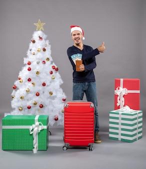 Lachender mann mit rotem koffer, der seine reisetickets hält und daumen auf grau macht