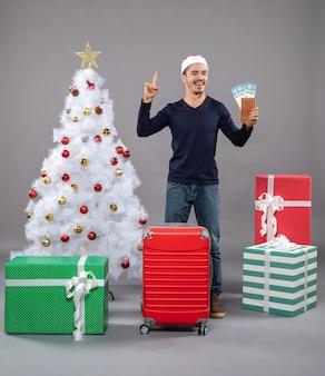Lachender mann mit rotem koffer, der seine reisetickets hält und etwas auf grau zeigt