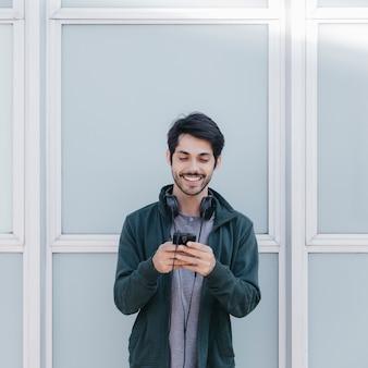 Lachender mann mit smartphone draußen