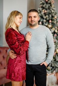 Lachender mann und frau genießen gemeinsam die neujahrsfeier zu hause. junges paar umarmt, kuschelt, feiert winterferien zusammen nahe geschmücktem weihnachtsbaum im wohnzimmer