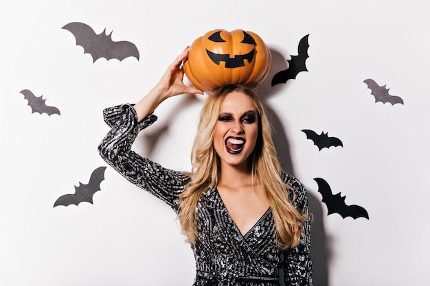 Lachender niedlicher vampir mit blondem haar, das kürbis hält. wunderschöne weiße frau in hexenkleidung, die spaß in halloween hat.