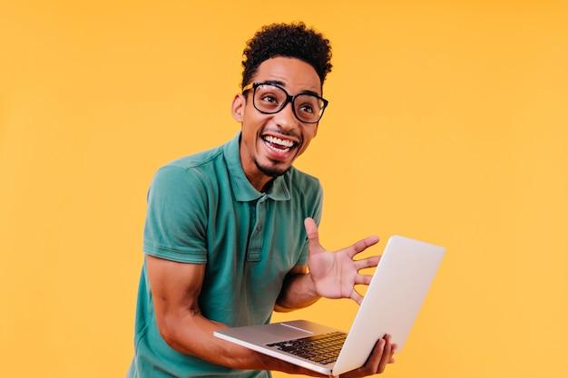 Lachender schwarzer mann in gläsern, die aufregung ausdrücken. emotionaler internationaler student, der computer hält.