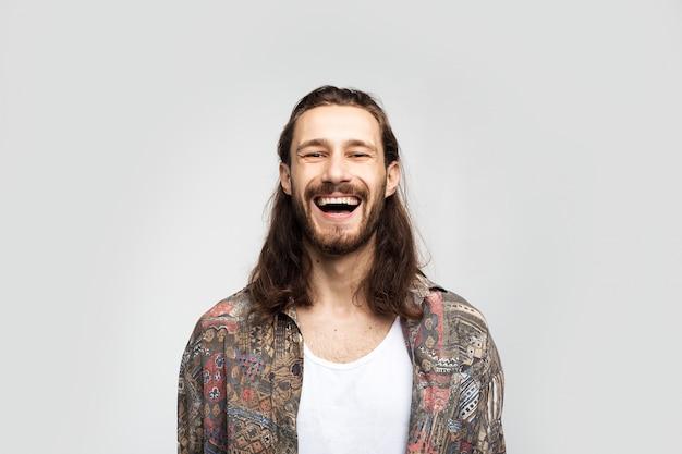 Lachender spaß sorgloser kerl, der auf platz für kopie wegschaut. stilvoller sorgloser mann des hipster-reisenden auf einem weißen studiohintergrund, menschenlebensstil