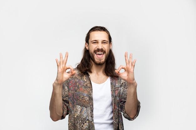 Lachender spaß sorgloser kerl zeigt geste ok. stilvoller sorgloser mann des hipster-reisenden auf einem weißen studiohintergrund, menschenlebensstil