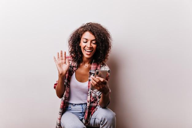 Lachendes afrikanisches mädchen, das während des videoanrufs lächelt. optimistische schwarze dame, die selfie auf weiß macht.