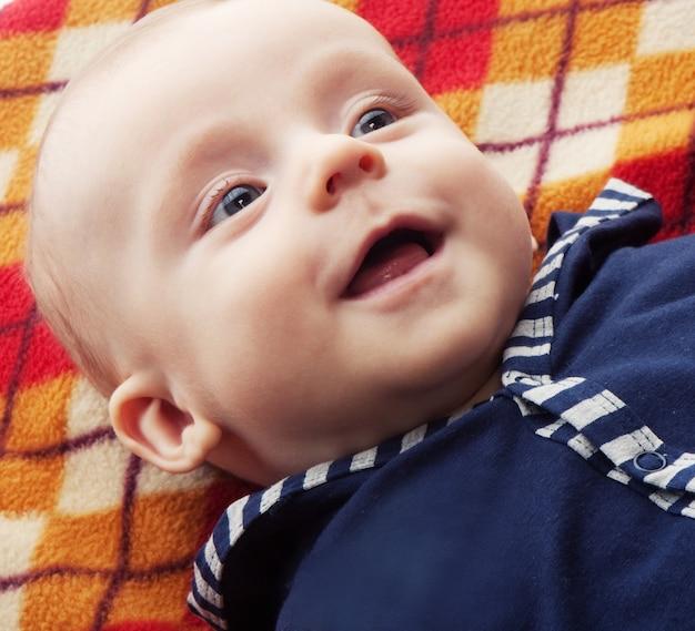 Lachendes baby auf dem boden auf einer decke