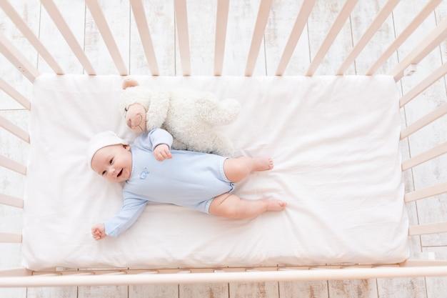 Lachendes baby in der krippe, niedliches baby 3 monate mit teddybärspielzeug, kinder und geburtskonzept