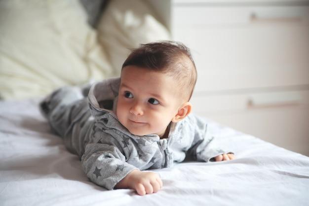 Lachendes baby kleines baby, das auf das bett im reinraum kriecht auf seinem gesichtsinteresse und -c $ wundern europäisch baby überrascht.